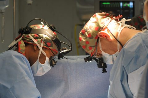 These doctors are in the operating room working on a heart stent procedure.