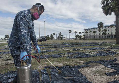 U.S. Navy applying permethrin spray to military uniforms