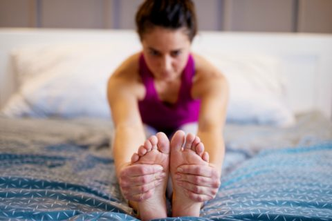 This is an example of the Seated Forward Bend Pose - simple yoga exercises for easy yoga in bed.